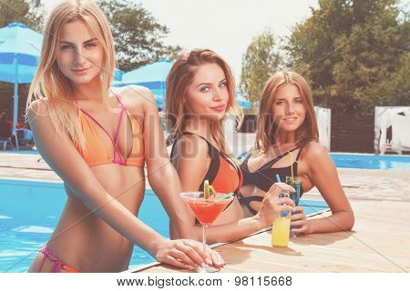 Three pretty girlfriends with cocktails at pool