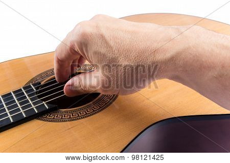 Man's Hand On Strings Of Classical Guitar On White