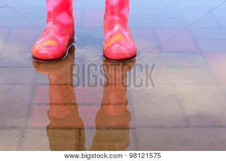 The Girl In Pink Boots Jumping In Puddles