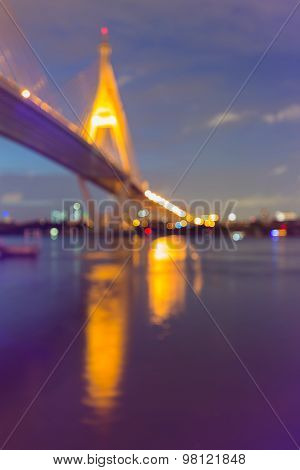 Blurred bokeh lights background of water reflection bridge and highway