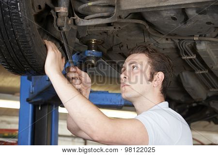 Mechanic Working On Wheel Underneath Car