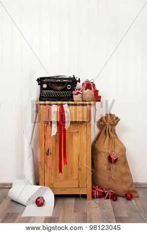 Writing christmas wishes with an antique typewriter. Vintage Xmas red and white decoration on old wooden background.