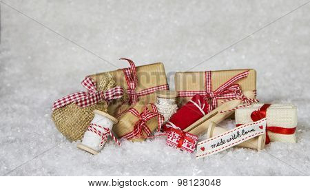 Homemade christmas presents wrapped in paper with ribbon and bows on snowy white and red background.