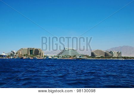 View of the tropical beach of Eilat with its luxury hotels on a clear blue sky