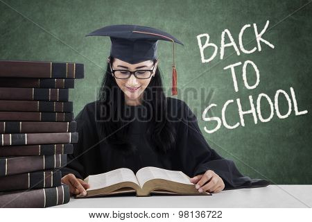 Beautiful Girl With Mortarboard Reading Book