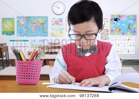 Elementary School Student Drawing On The Paper
