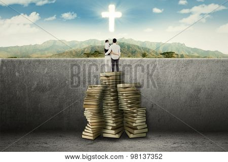Family Using Book To Guide And See A Cross