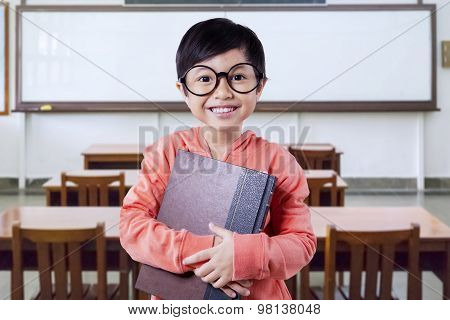 Little Schoolgirl With A Book In The Class