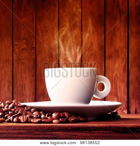 Cup of coffee with coffee beans on a beautiful brown background.Filtered image: vintage effect.