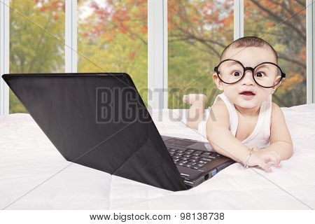 Smiling Baby With Laptop And Glasses