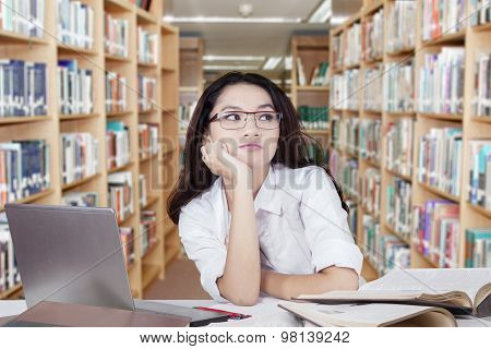Thoughtful Schoolgirl With Long Hair In Library
