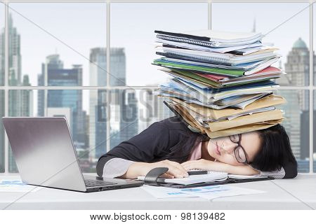 Tired Female Worker With Paperwork On Head