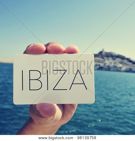 the hand of a young caucasian man showing a signboard with the word Ibiza, written in it, with Dalt Vila district of Ibiza Town in the background, in the Balearic Islands, Spain; filtered