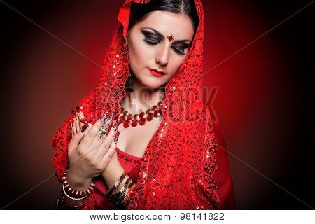beautiful girl in the image of Indian woman in a red sari with beautiful patch acrylic nails