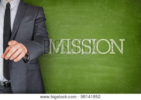 Mission on blackboard with businessman