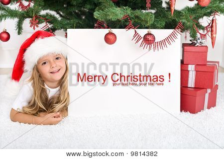 Little Girl Under The Christmas Tree With Banner