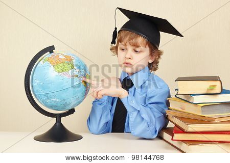 Little serious boy in academic hat showing on globe among old books