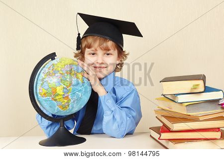 Little boy in academic hat with a globe among old books