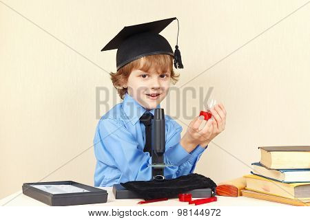 Little professor in academic hat with the jars for research next to microscope