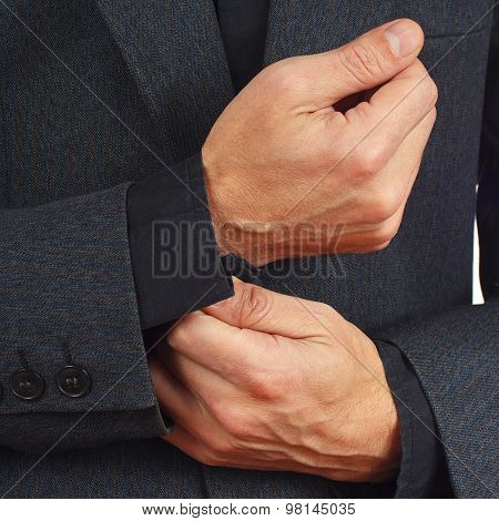 Stylish man unbuttons his sleeve business suit closeup