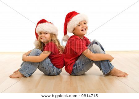 Happy Kids On The Floor Wearing Christmas Hats