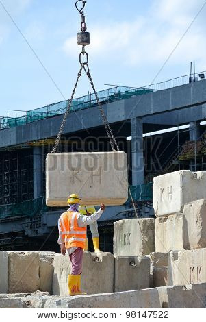 Construction workers hoisting load test block at the construction site