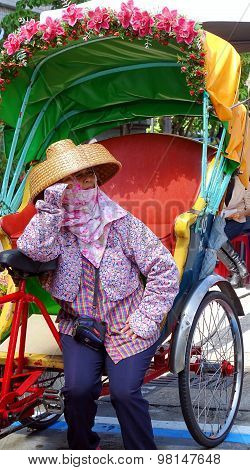 Female Pedicab Driver Waits For Customers