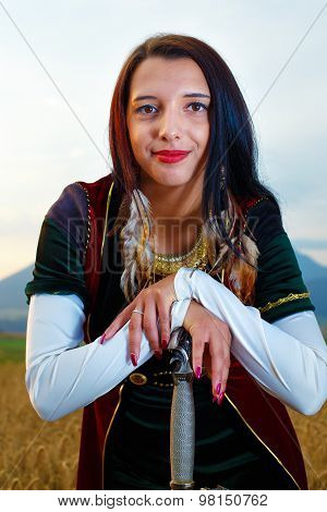 Smiling Young woman with ornamental dress and sword in hand  with sunset. Natural background.
