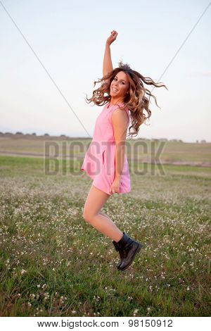 Pretty woman dressed in pink jumping on a flowery meadow