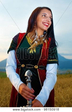Smiling Young woman with ornamental dress and sword in hand  with sunset. Natural background..