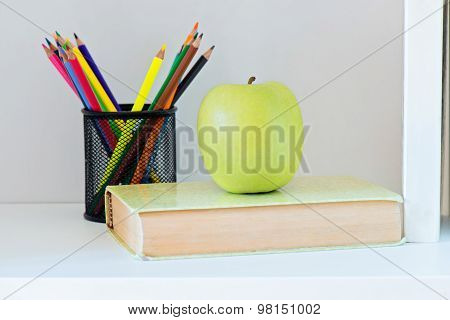 A yellow apple sitting on top of book