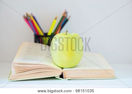 A yellow apple sitting on opened book