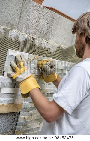 Builder Tiling A Wall