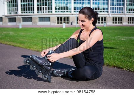 Happy Woman Sitting And Putting On Inline Skates