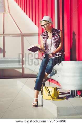 Toned Shot Of Stylish Woman Sitting On Street And Reading Book