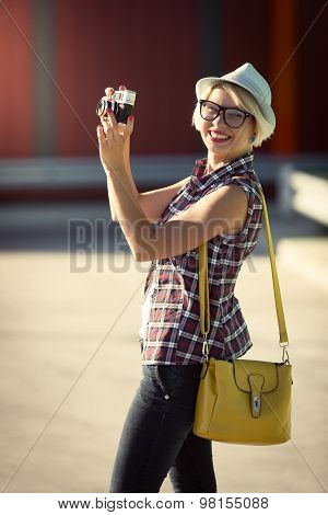 Hipster Girl Walking On Street And Making Photo Of Retro Camera