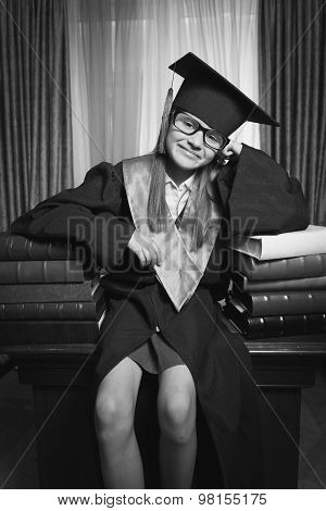 Portrait Of Smart Girl In Graduation Cap Posing On Table At Library
