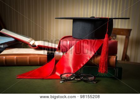 Graduation Cap And Red Ribbon Lying On Book At Library