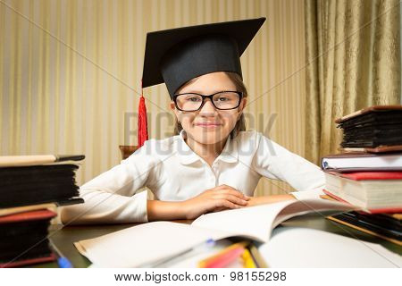 Portrait Of Smiling Little Girl In Graduation Hat Sitting At Table