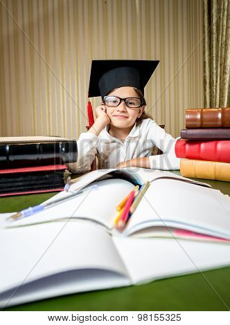Cute Girl In Graduation Cap Sitting At Table And Doing Homework
