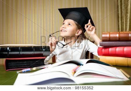 Smart Thoughtful Girl Posing At Desk In Graduation Cap