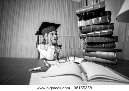 Smart Girl In Graduation Cap Looking At High Heap Of Book