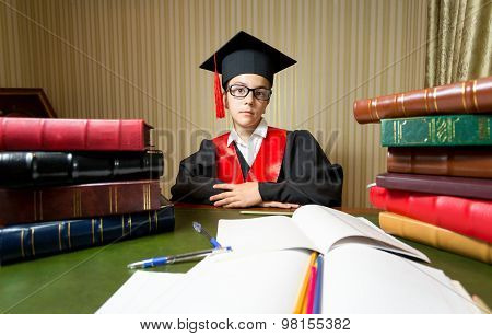 Girl In Graduation Cap And Black Gown Sitting At Library