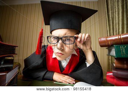 Smart Girl In Graduation Cap And Eyeglasses Looking At Camera