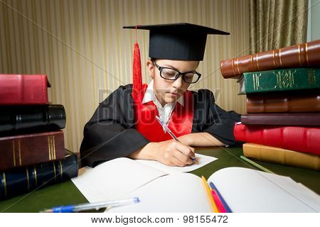 Portrait Of Girl In Graduation Cap Doing Homework At Library