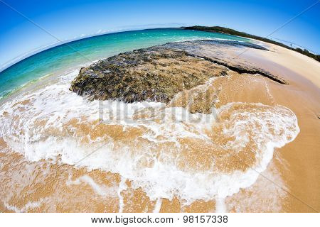 Close up of a reef on the shore of a tropical white sand beach with gentle surf spilling over