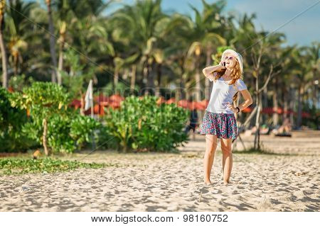 Beautiful young caucasian woman at the beach in white hat talking on mobile phone and laughing