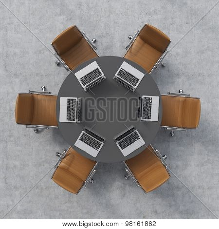Top View Of A Conference Room. A Black Round Table, Six Brown Leather Chairs And Six Laptops. Office