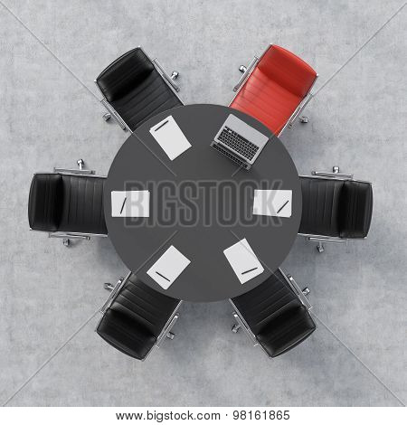 Top View Of A Conference Room. A Black Round Table, Six Chairs, One Of Them Is Red. A Laptop And Fiv