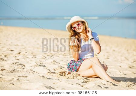 Beautifil young woman on the beach at sunny day taking selfie with phone